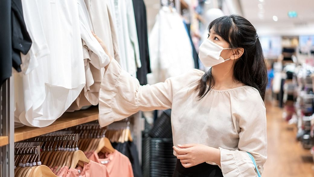 Asian woman wearing mask over her face while choosing shirt at s