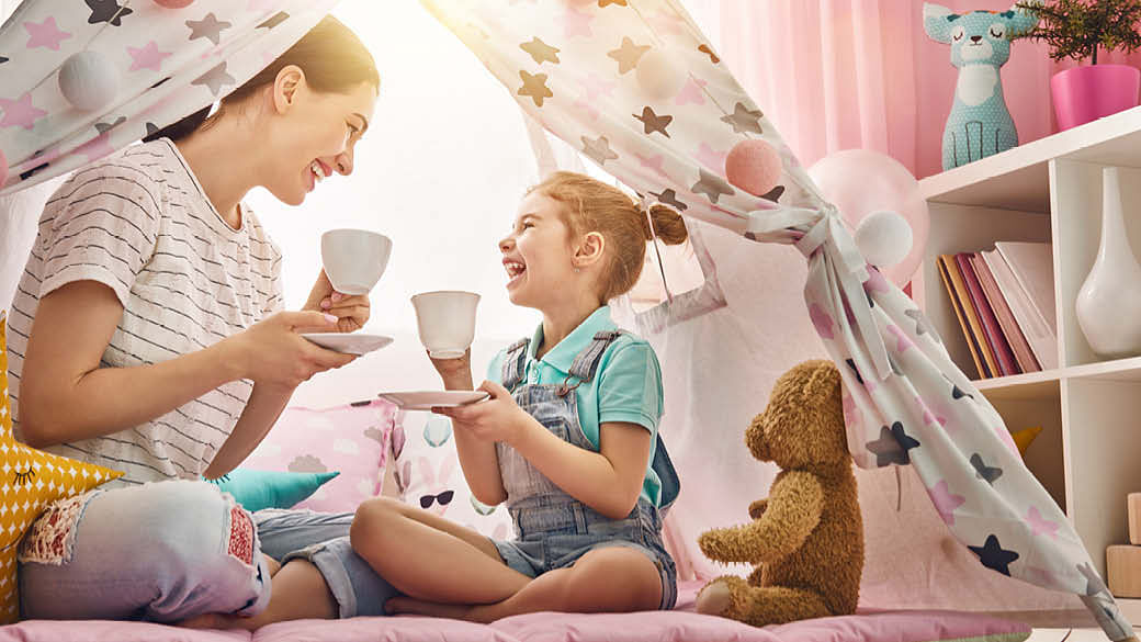 A mother and daughter having tea in a teepee tent.
