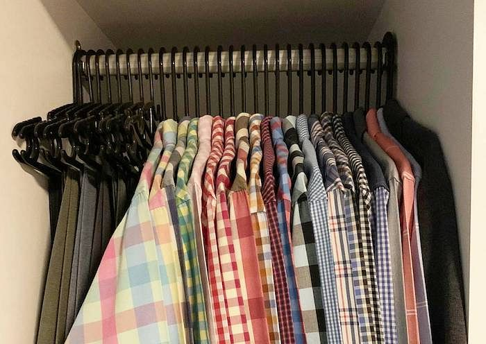 His rack of checkered shirts that he uses for work, all neatly hung.