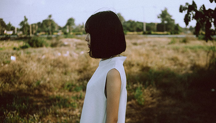 Short haired asian woman looking into the distance in a farm