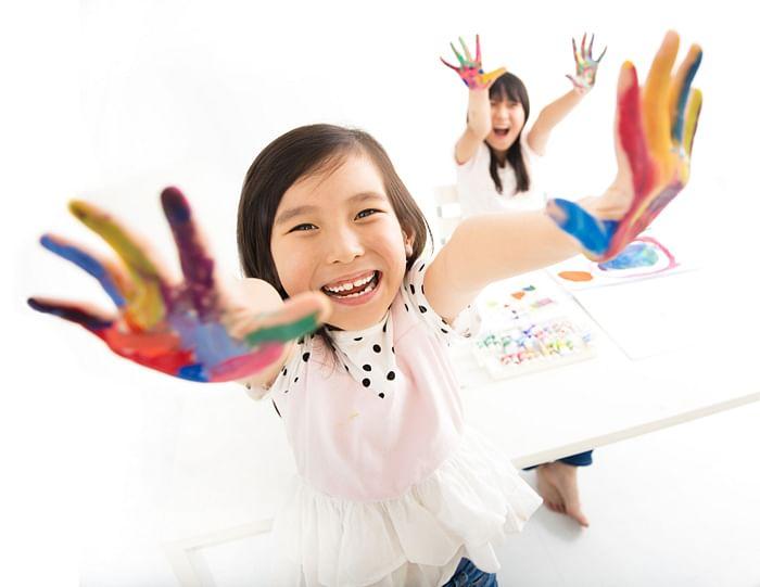 Happy laughing children paint hands