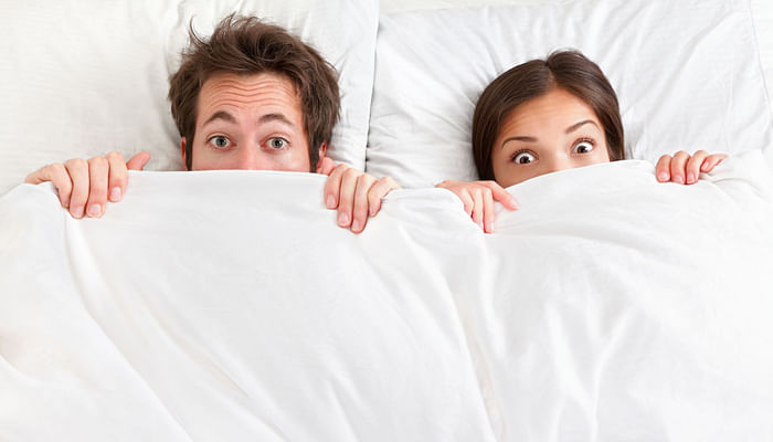 awkward couple in bed with sheets pulled to the nose