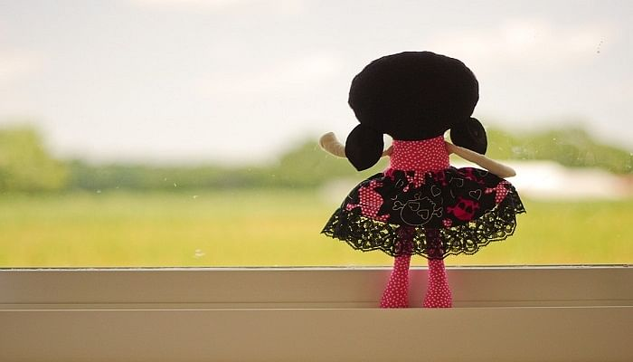 back of a doll looking out of the window