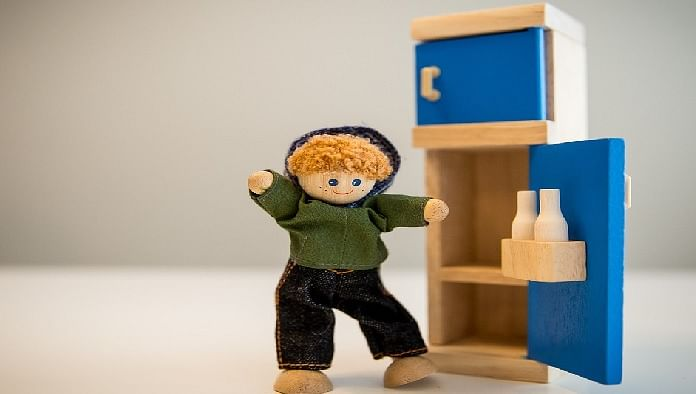 cute wooden toy boy with a wooden refrigerator with door open
