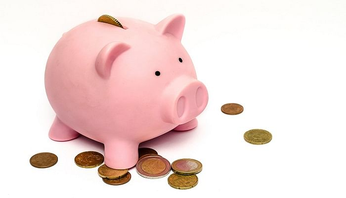 pink piggy bank with money scattered around