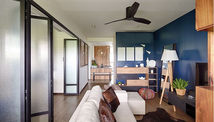 A modern HDB flat with sliding doors separating the bedroom and living room