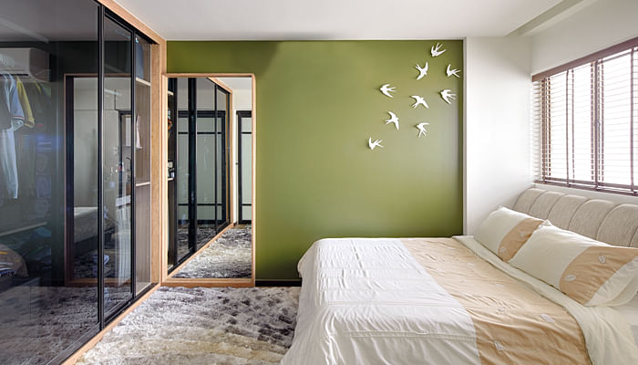 Bedroom of a HDB flat with a fresh green feature wall.