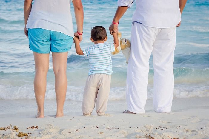 back view of a family of three at the beach