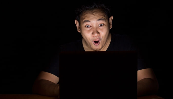 man-looking-shocked-and-excited-in-front-of-his-laptop-in-the-dark