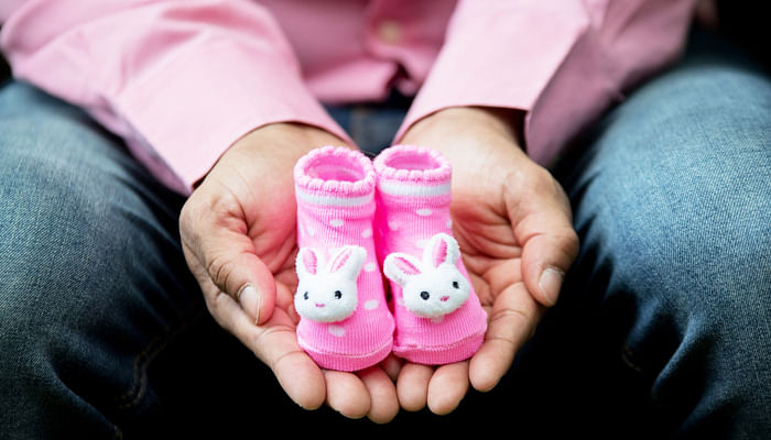expecting father holding baby booties