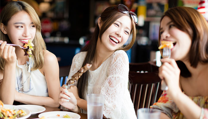 Happy women dining eating together at a restaurant