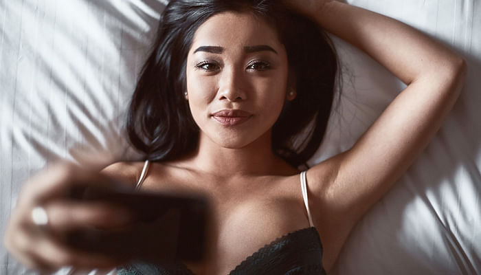 beautiful-sensual-asian-woman-in-underwear-lying-on-the-bed-with-the-phone-in-his-hand