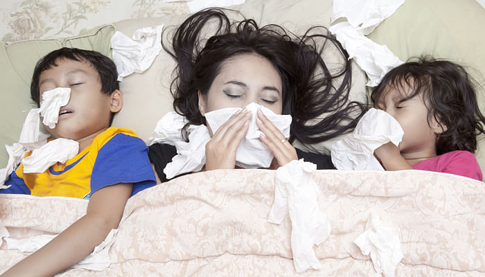 Woman and kids down with flu in bed