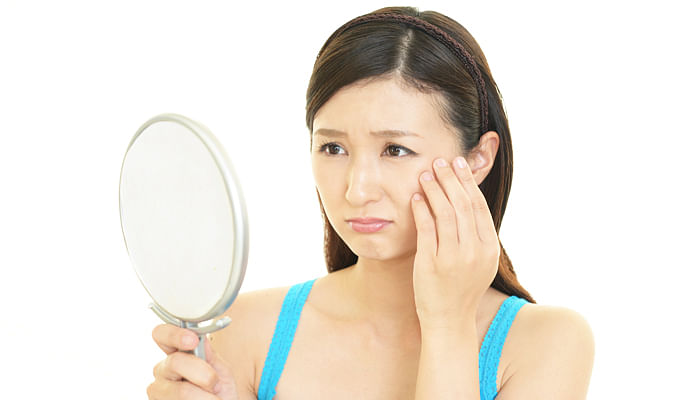 woman-looking-at-mirror-unhappy-with-skin