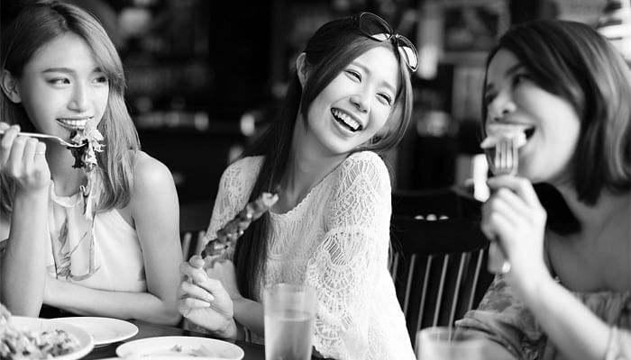 Happy-women-dining-eating-together-at-a-restaurant-BW
