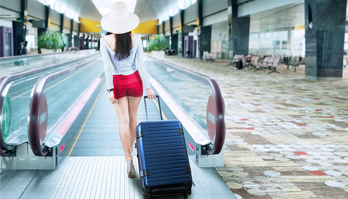 8018440-young-Korean-woman-with-a-suitcase-walking-to-escalator-at-airport