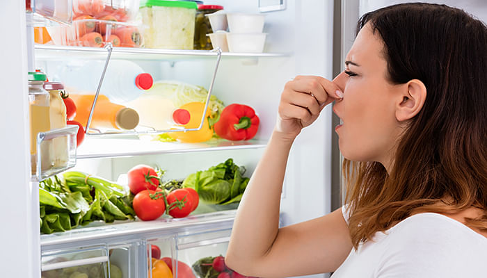 woman-checking-smelly-spoilt-foods-in-fridge