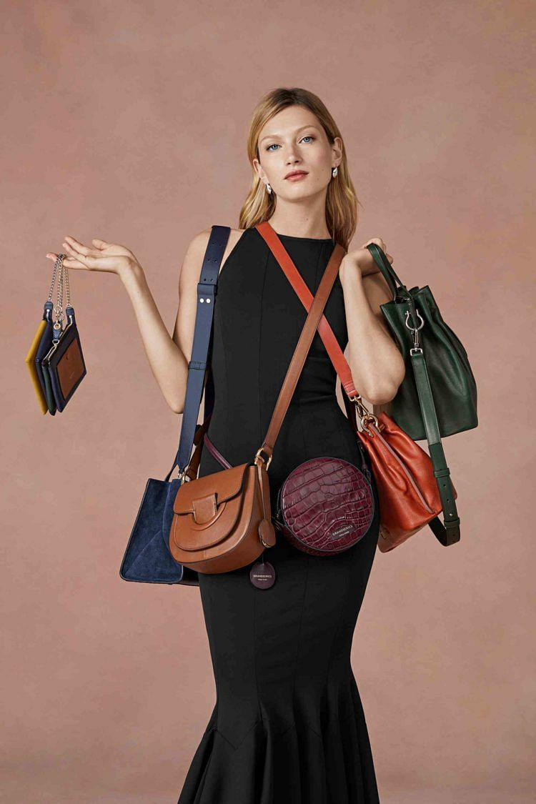 Cole Haan model shot with Grand Ambition bags
